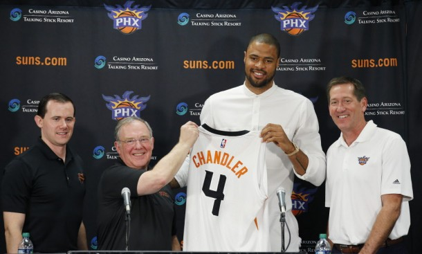 Flanked by Phoenix Suns head coach, Jeff Hornacek, right, general manager Ryan McDonough, left, and senior adviser Lon Babby, second from left, Suns' Tyson Chandler, the newly signed free agent, holds up his new uniform after being introduced to the media during a news conference Thursday, July 9, 2015, in Phoenix. (AP Photo/Ross D. Franklin)